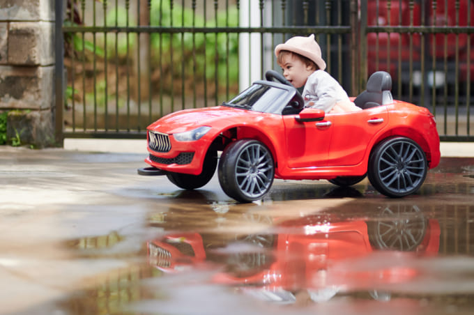 Small baby girl driving toy car