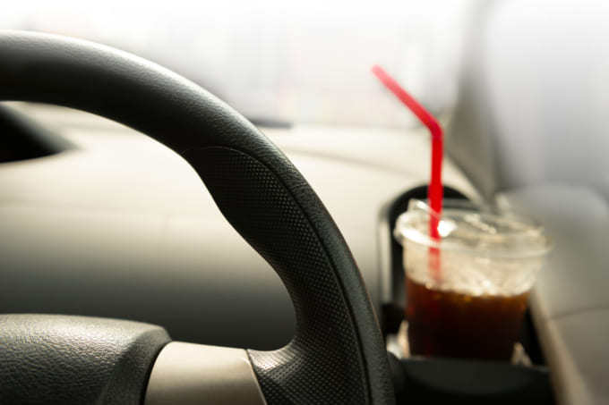 part of car steering wheel with cold take away black coffee for