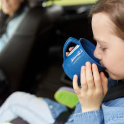 little girl driving in car and drinking from cup