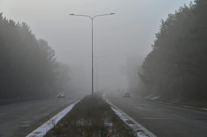 Cars in the fog. Bad winter weather and dangerous automobile traffic on the road. Light vehicles in foggy day.