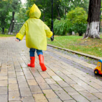 Cute little boy in yellow raincoat running with toy truck under rain at park