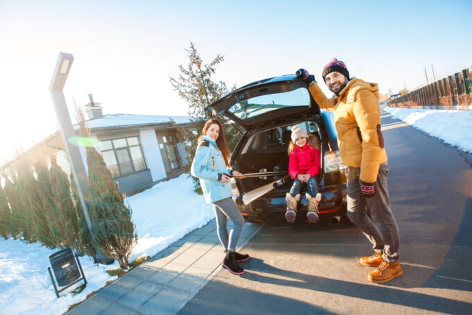 Winter vacation. Family time together outdoors standing near car putting ski equipment into trunk smiling excited