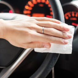 woman hand cleaning on steering wheel in his car, against Novel